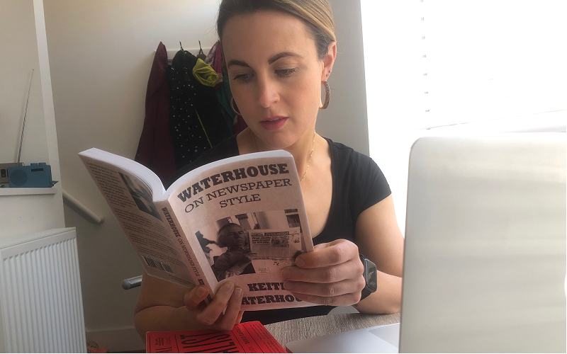 News Associates Manchester part-time trainee Gemma Corby wearing a black t-shirt with her dark blonde hair tied back and hoop earrings sitting down reading Waterhouse on Newspaper Style by Keith Waterhouse in front of a laptop.