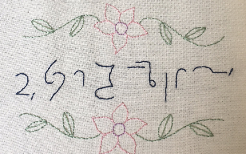 The sentence 'Good evening ladies and gentlemen and welcome to this parish council meeting' in Teeline shorthand sewn into a white cloth in blue thread surrounded by sewn in green leaves and light pink flowers.