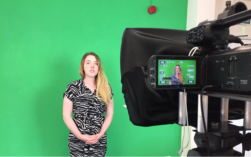 Trainee being filmed in front of a green screen