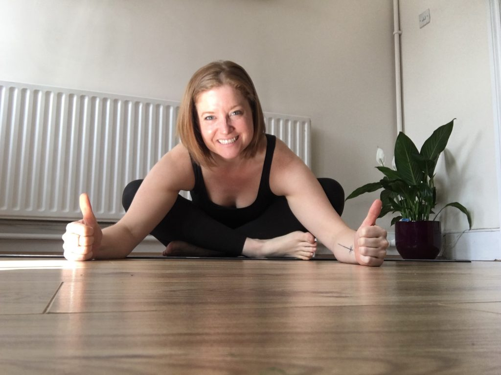 Yoga teacher Emma poses with her thumbs up