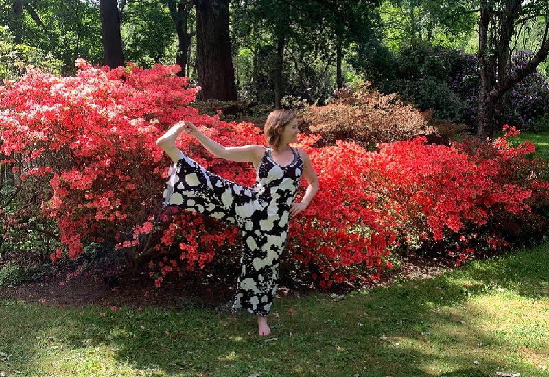 Yoga teacher Emma stretches in front a flowery bush