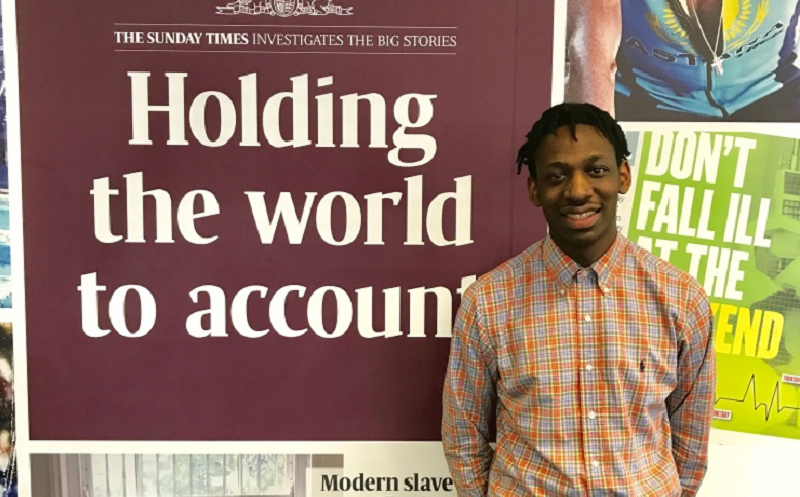 """NCTJ-accredited journalist Shingi is standing in front of a Sunday Times banner which reads """"Holding the world to account"""""""