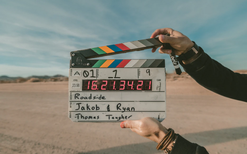 Featured image included is of someone holding up a movie clapper, with a desert scene in the background and a blue sky