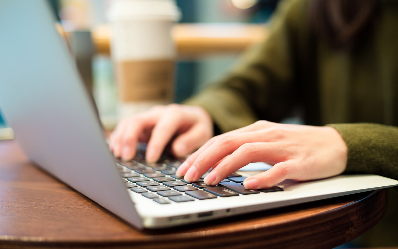 Stock photo of someone typing on a laptop, wooden desk, person is wearing a green jumper